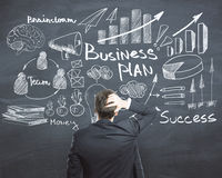 Strategy concept. Back view of stressed young businessman on chalkboard background with business sketch. Strategy concept Stock Photo