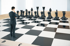 Strategy concept chess. Strategy concept with thinking businessman and black chess pieces standing on huge chessboard with interior in the background. Sideview Royalty Free Stock Image