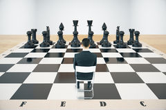 Strategy concept chessboard and businessman. Strategy concept with sitting businessman and black chess pieces on huge chessboard with concrete wall in the Royalty Free Stock Images