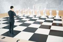 Strategy concept chessboard. Strategy concept with thinking businessman and white chess pieces standing on huge chessboard with concrete wall in the background Royalty Free Stock Images
