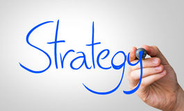 Strategy hand writing with a blue mark on a transparent board Stock Image