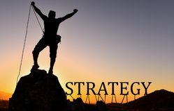 Strategy. Man seen in silhouette on mountain top arms extended, at sunset with a rope holding the text 'strategy'  in uppercase letters, background golden sky Stock Photos