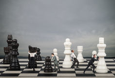 Strategy and tactics in business. Businessmen move the chess pieces. Strategy and tactics in business concept Royalty Free Stock Photo