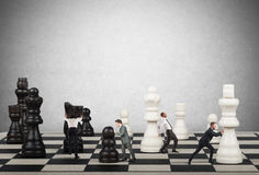 Strategy and tactics in business. Businessmen move the chess pieces. Strategy and tactics in business concept Royalty Free Stock Image