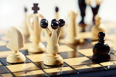 Strategy and tactics in a game of chess. With a wooden chessboard full of chess pieces and focus to a light wood king in the foreground Stock Photo