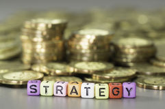 Strategy text and Gold coins Royalty Free Stock Photos