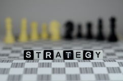 STRATEGY word. Placed on top of chess board with chess pawn on the background Stock Photography