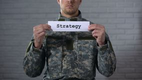 Strategy word written on sign in hands of male soldier, battle plan, defense. Stock footage stock video footage