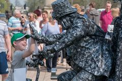 Living statue high fives young boy royalty free stock photography