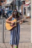 Dark haired female singer on street with sunglasses and stock image