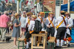 Group of morris dancers relax in between performances with a beer stock photography