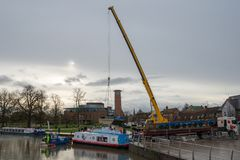 Crane lifting boat into canal stock image