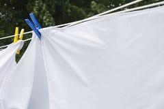 Strati bianchi che si asciugano su un filo stendiabiti fotografia stock
