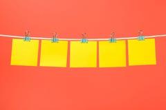 Strati di carta gialli in bianco sulla corda Fotografie Stock