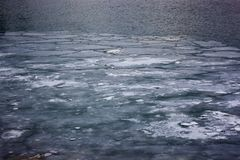 Strati di ghiaccio che galleggiano giù il Detroit River a Windsor, lungofiume di Ontario Immagini Stock