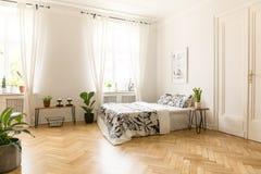 Strati modellati sul letto sotto il manifesto in camera da letto luminosa spaziosa Fotografia Stock Libera da Diritti