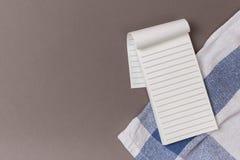 Strati vuoti del taccuino aperto su un fondo e su un asciugamano blu puliti fotografie stock