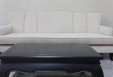strato beige del sofà del tessuto e scrittorio nero Fotografie Stock
