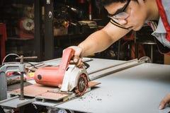 Strato composito di alluminio di taglio dell'uomo del meccanico con il mackintosh della macinazione fotografie stock
