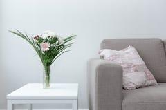 Strato con il cuscino accanto alla tavola della decorazione moderna del salone dei fiori contro fondo bianco immagine stock libera da diritti