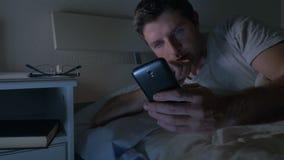 Strato del giovane a letto a casa tardi alla notte facendo uso del telefono cellulare alla scarsa visibilità rilassata in tecnolo