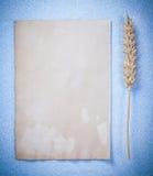 Strato di carta d'annata delle orecchie del grano sull'immagine blu di verticale del fondo Immagine Stock