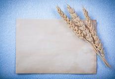 Strato di carta d'annata delle orecchie dorate del grano su fondo blu Immagine Stock