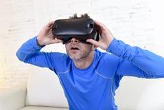 Strato felice del sofà del salone dell'uomo a casa eccitato facendo uso degli occhiali di protezione 3d che guardano realtà virtu Immagini Stock