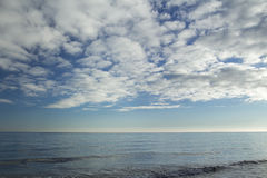 Stratocumulus clouds over blue sea water waves. Stratocumulus clouds over navy blue sea water waves Stock Image
