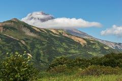 Stratovolcano de Vilyuchinsky dans les nuages Vue de brookvalley Spokoyny au pied de la pente du nord-est externe de Photos stock