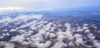 Stratus cloud aboce ground view from airplane. Underneath is the urban view Royalty Free Stock Image