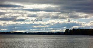 Stratus stratocumulus altostratus clouds over a dark lake, climate change. Sky filled with menacing clouds threatening rain over a gray lake on a dark day threat royalty free stock photography