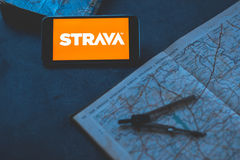 Strava application on the phone on a dark background with map. royalty free stock photo