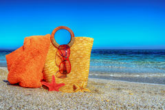 Straw bag, beach towel and sunglasses on the sand Stock Photo