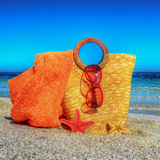 Straw bag, beach towel and sunglasses on the sand Royalty Free Stock Photo