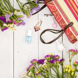 straw bag, colorful flowers, cosmetics makeup, bijou and essentials on white wooden background Royalty Free Stock Photography