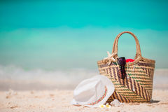 Straw bag, fist star, headphones, hat and sunglasses on white beach Royalty Free Stock Photography
