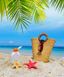 Straw bag and suntan bottle under a palm tree Stock Photography