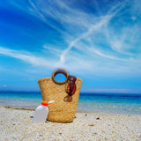 Straw bag and suntan lotion bottle under a cloudy sky Stock Image