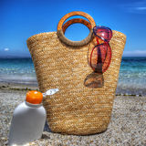 Straw bag and suntan lotion by the sea in hdr Stock Photo