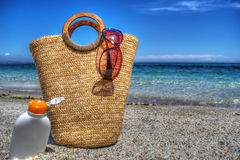 Straw bag and suntan lotion by the sea in hdr Stock Photography