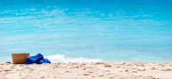 Straw bag and towel at beach Stock Photos