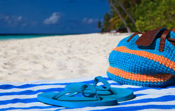 Straw bag, towel and flip flops on a tropical beach Stock Photo
