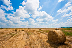 Straw bale / hey stack. On golden sunny day with big clouds and blue skies in the background royalty free stock image