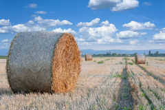 Straw bale / hay stack on sunny day with white clouds. Straw bale / hay stack on golden sunny day with white clouds in the background Stock Image