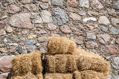 Straw bale on wall made of stones Stock Photo