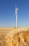 Straw bale with a wind turbine behind. Detail of a straw bale in a field with an out-of-focus eolic generator behind, under the warm light of a summer evening in Royalty Free Stock Image