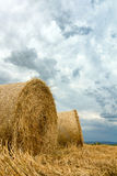 Straw bales on farmland Storm clouds. Royalty Free Stock Image
