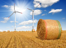 Straw bales on farmland with wind turbine Royalty Free Stock Image