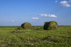 Straw bales on a field in the foreground.  Harvest of hay. Clouds in the sky. Agricultural farm. Hills with cultivated fields and. Straw bales on a field in the royalty free stock photography